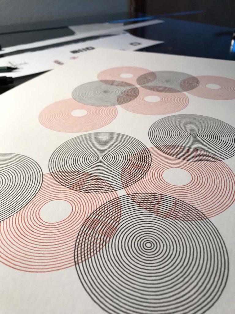 Circulos concentircos en tinta roja y tinta negra vistos de cerca.